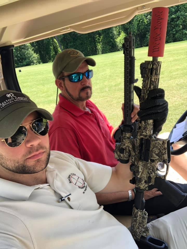 Owners in a golf cart holding an AR15